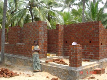 Mariamal in front of her house under construction